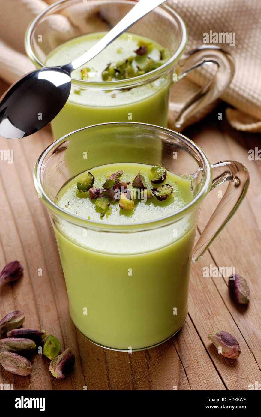 pistachio pudding into glass cup - Stock Image