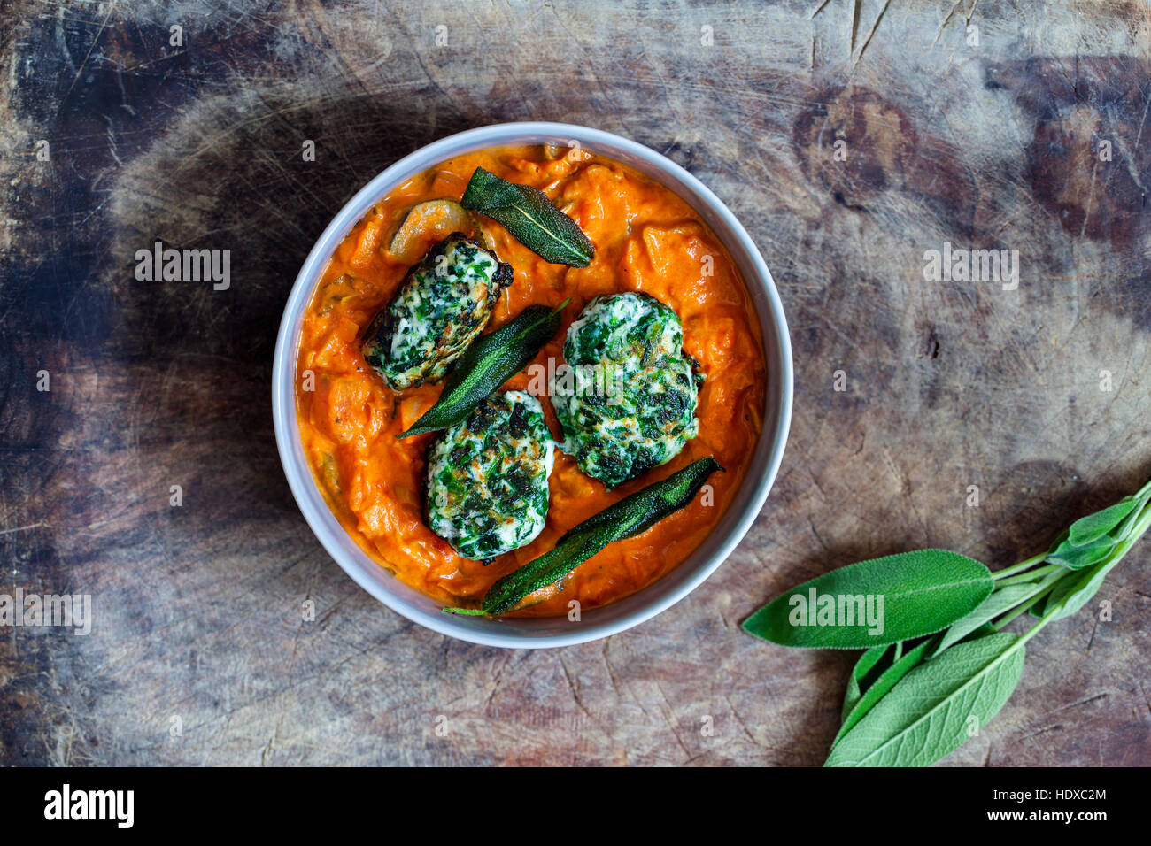 Spinach and ricotta dumplings in tomato and courgette sauce - Stock Image