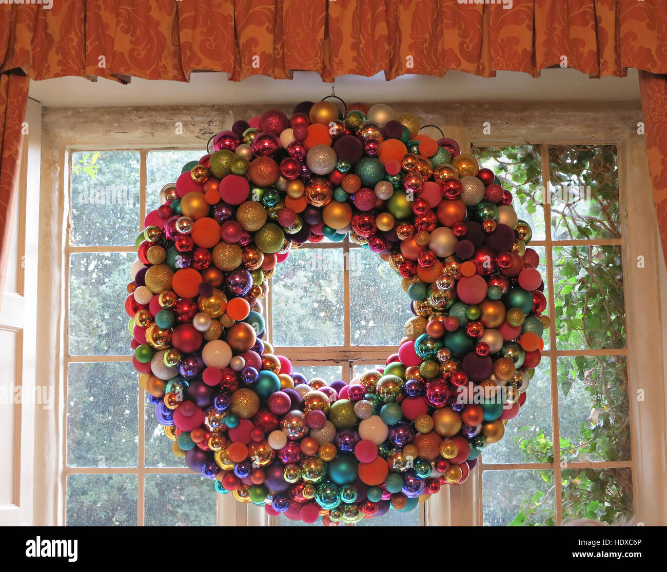 large christmas wreath made of multi coloured baubles hanging in window stock image - Large Christmas Wreath
