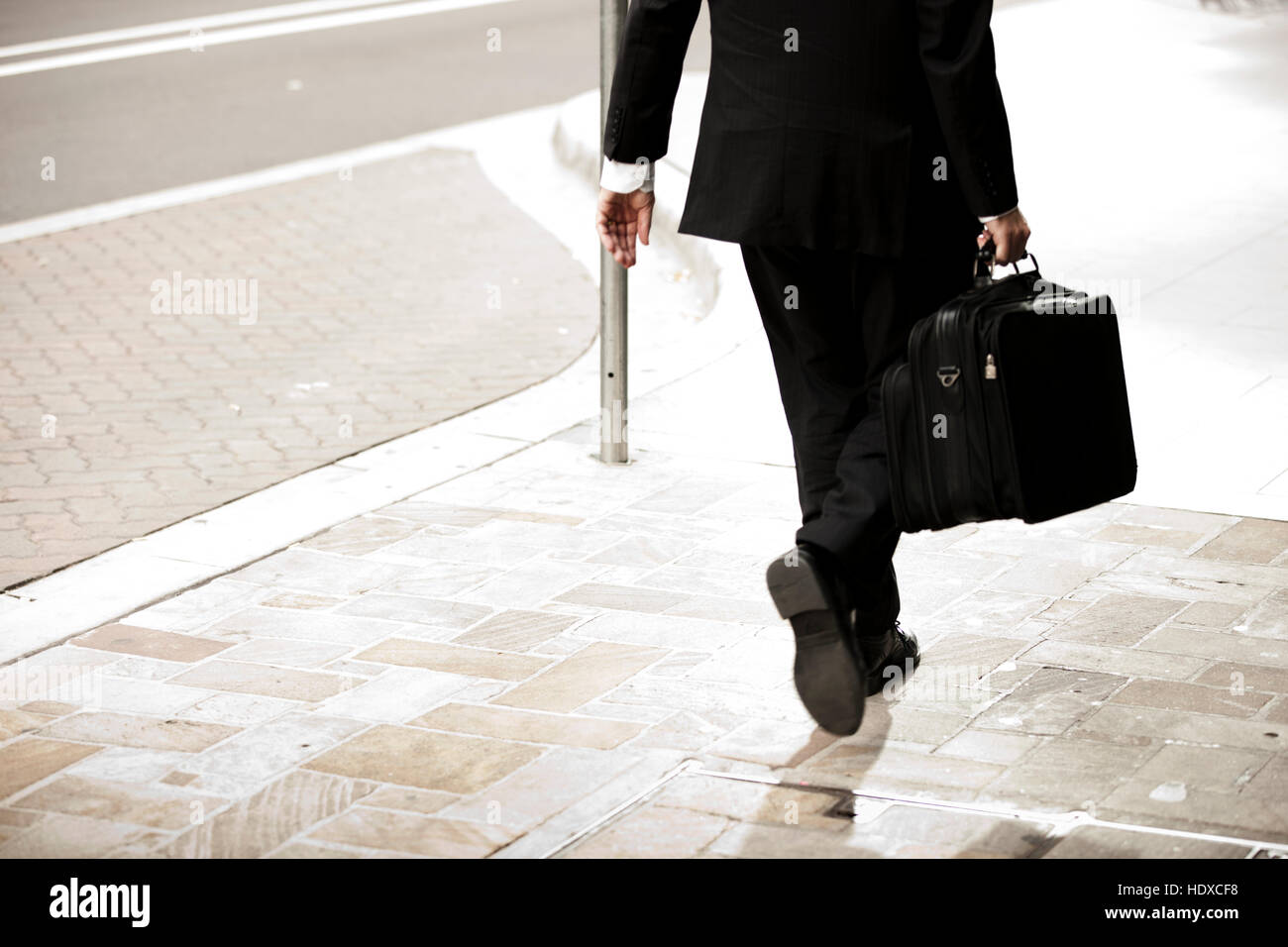 Business man in a suit holding briefcase walking down street - Stock Image