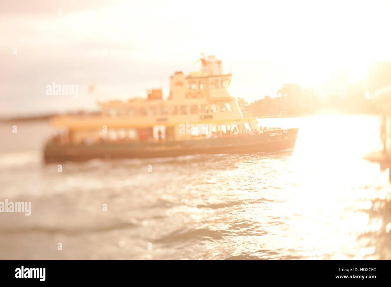 Select focus tilt-shift image of harbor ferry in Sydney Harbor during sunset - Stock Image