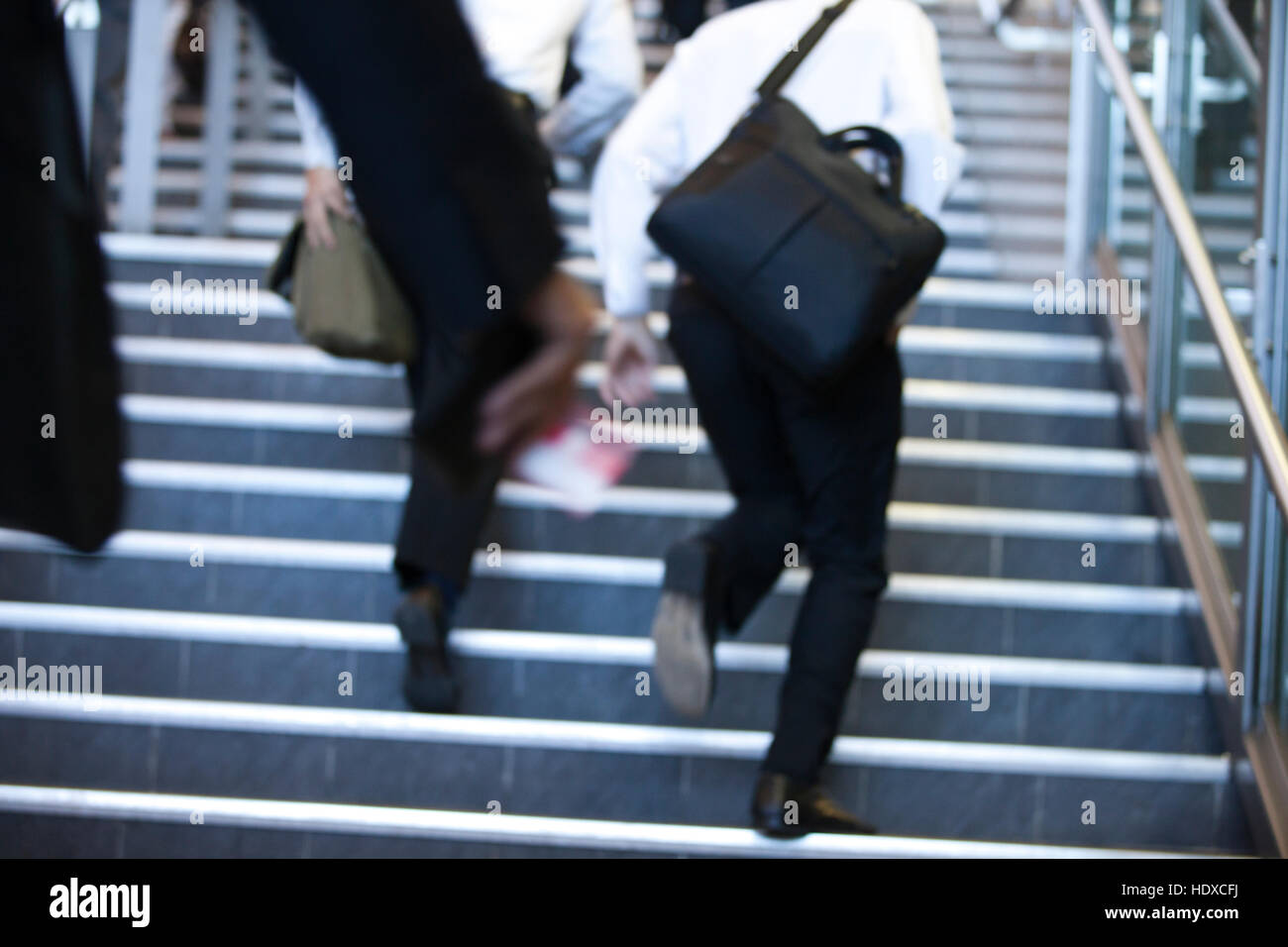 Business commuters run up stairs in a rush to work - Stock Image