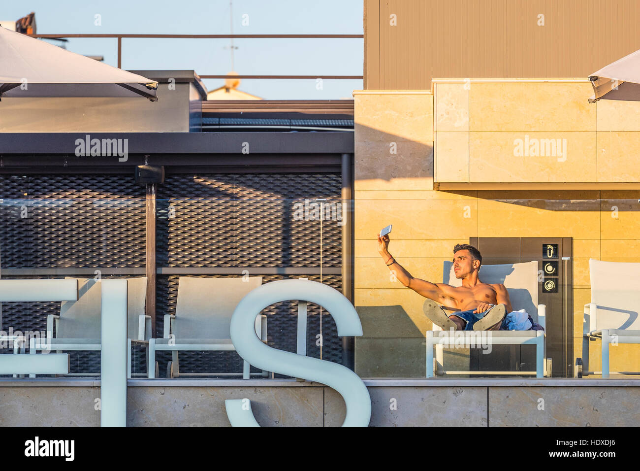 A 20s something bare-chested male on the top floor pool space of a Barcelona hotel takes selfies of himself using Stock Photo
