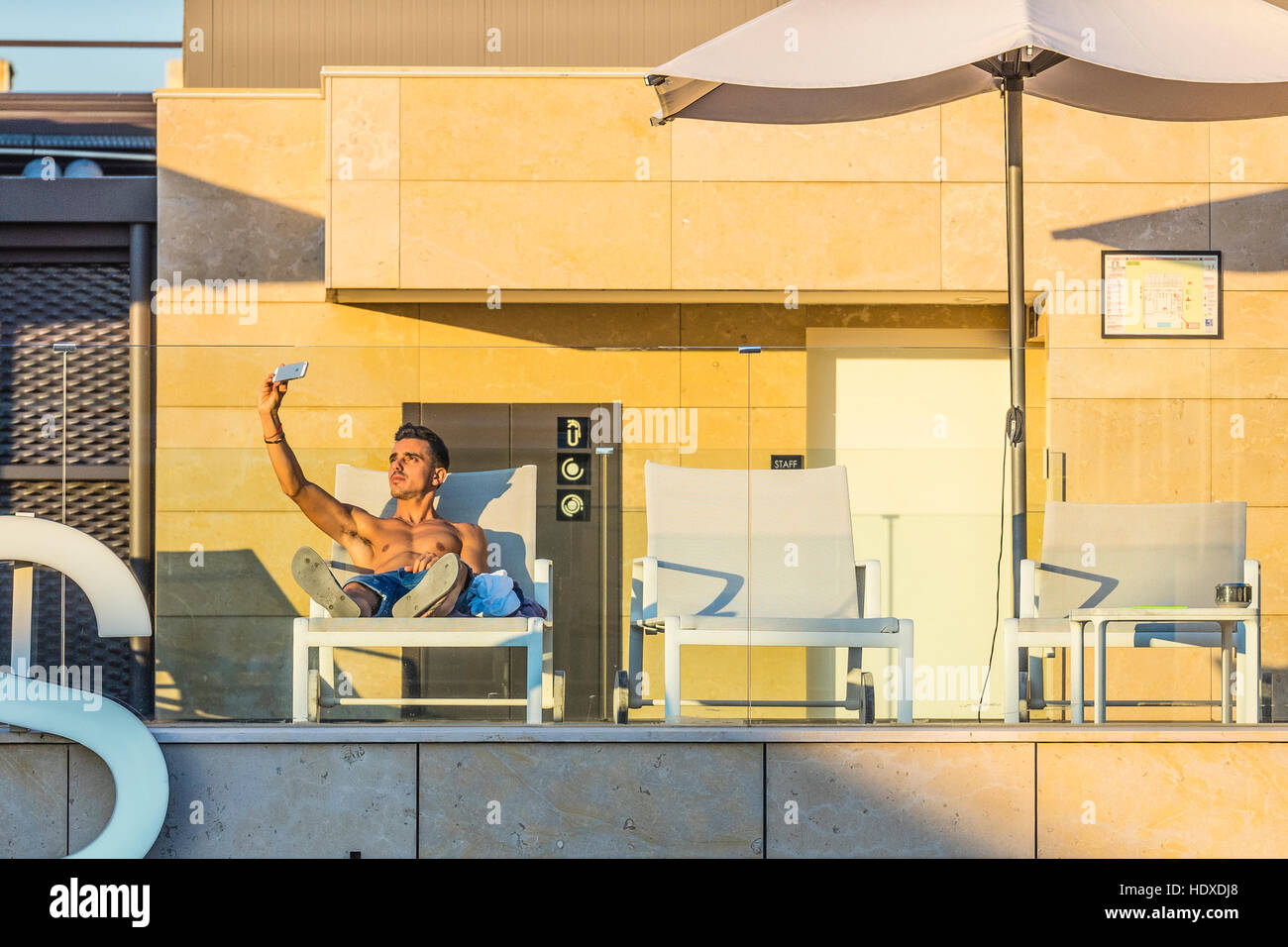 A 20s something bare-chested male on the top floor pool space of a Barcelona hotel takes selfies of himself using - Stock Image