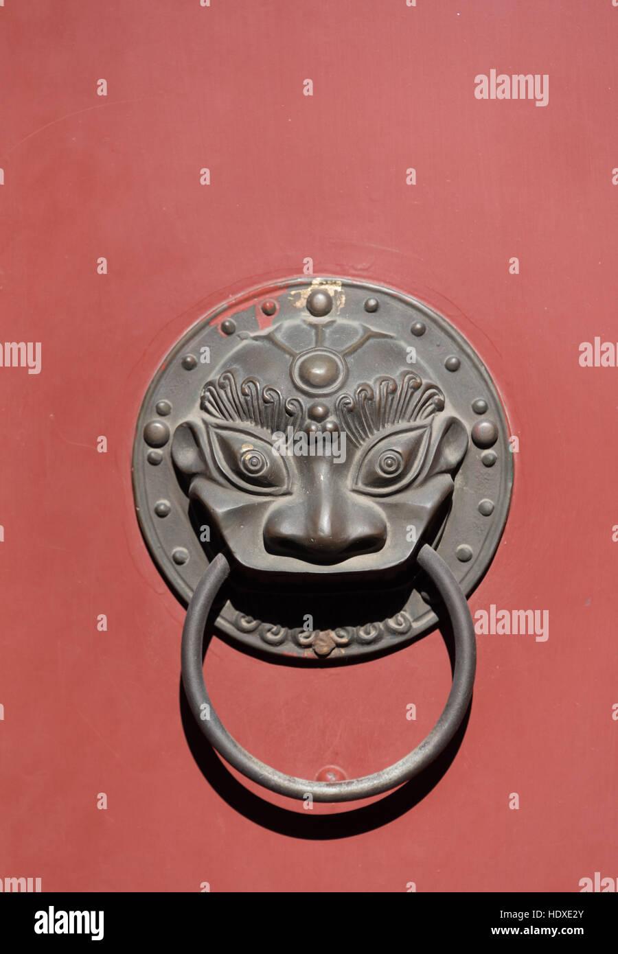 Chinese door knocker on red door in a Beijing hutong, China. - Stock Image