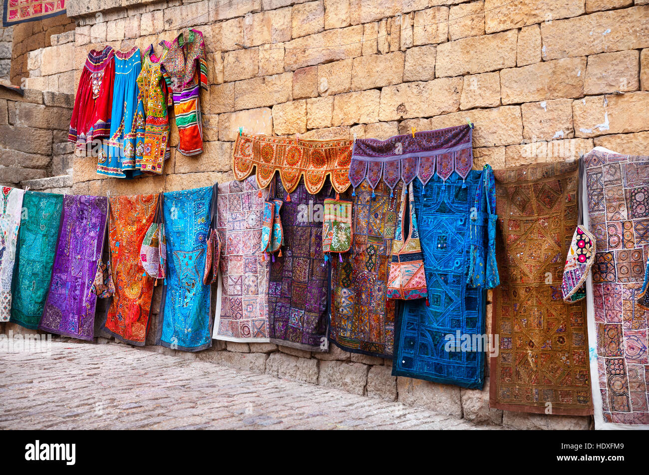 City street market with traditional clothes on the wall of Jaisalmer fort in Rajasthan, India Stock Photo