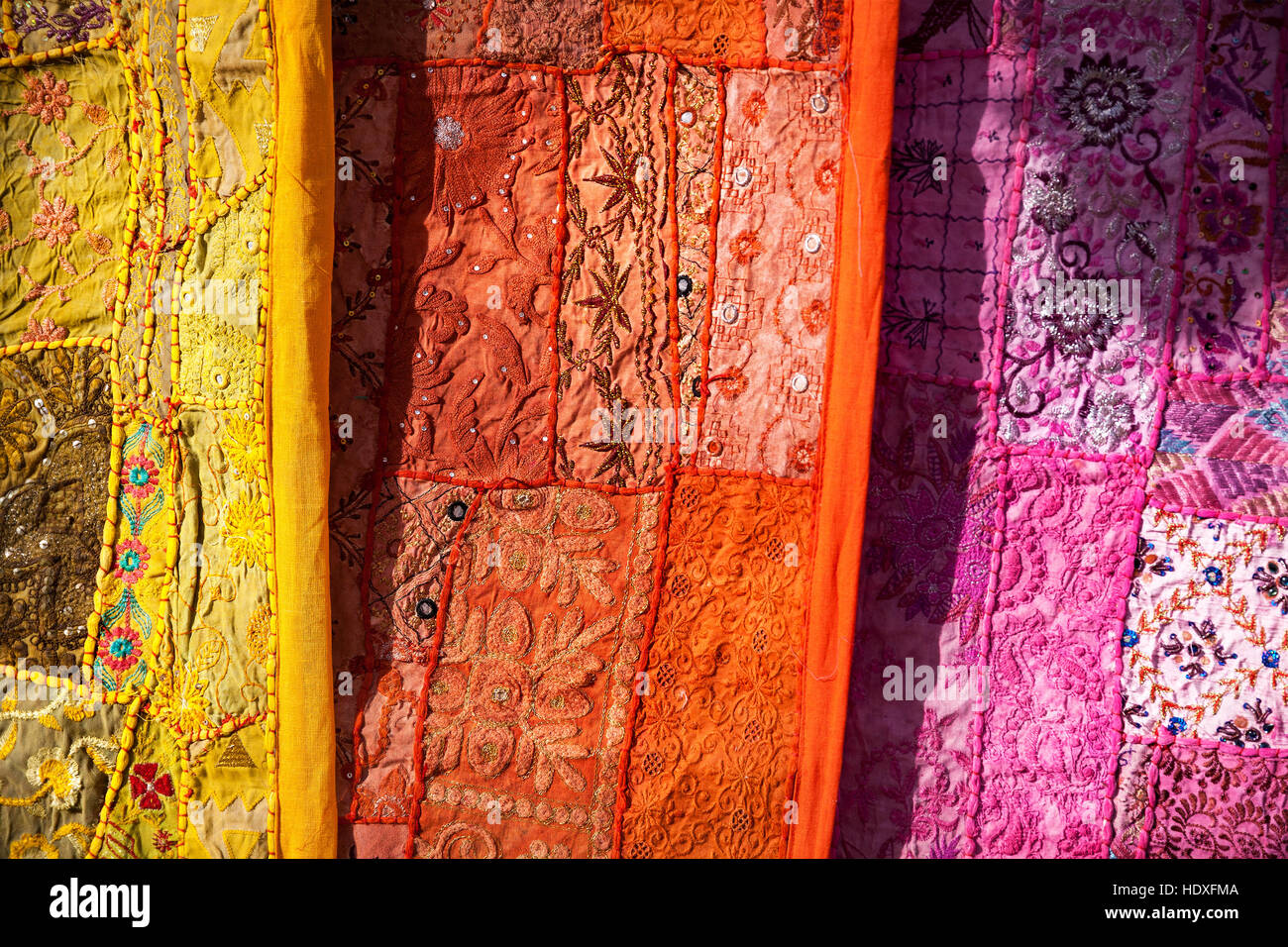City street market with traditional clothes on the wall of Jaisalmer fort in Rajasthan, India - Stock Image