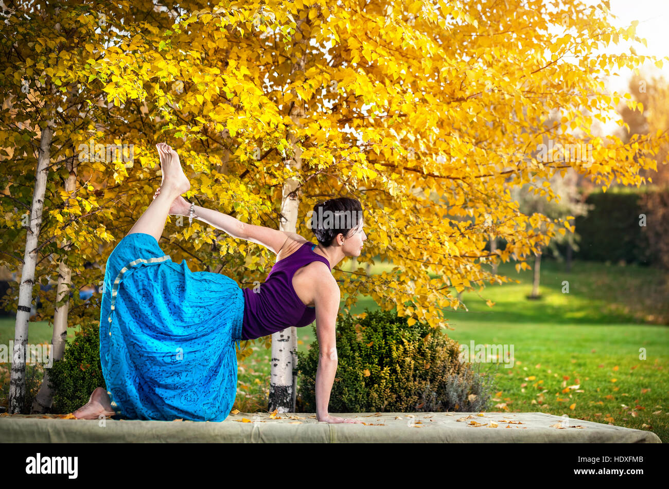 Young woman doing yoga in autumn city park near yellow birch trees - Stock Image