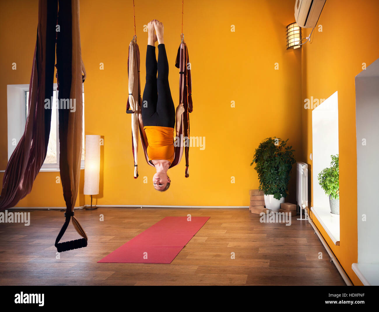 Young woman doing antigravity yoga upside down position in fitness club with yellow walls - Stock Image