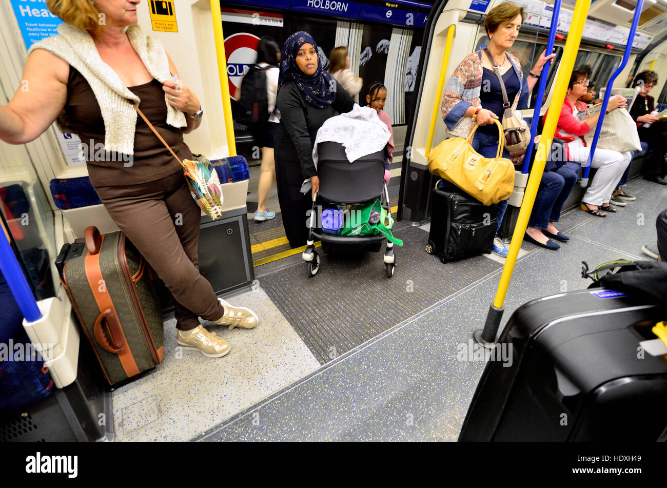 London, England, UK. Muslim woman getting on a tube train with a pram and a child Stock Photo