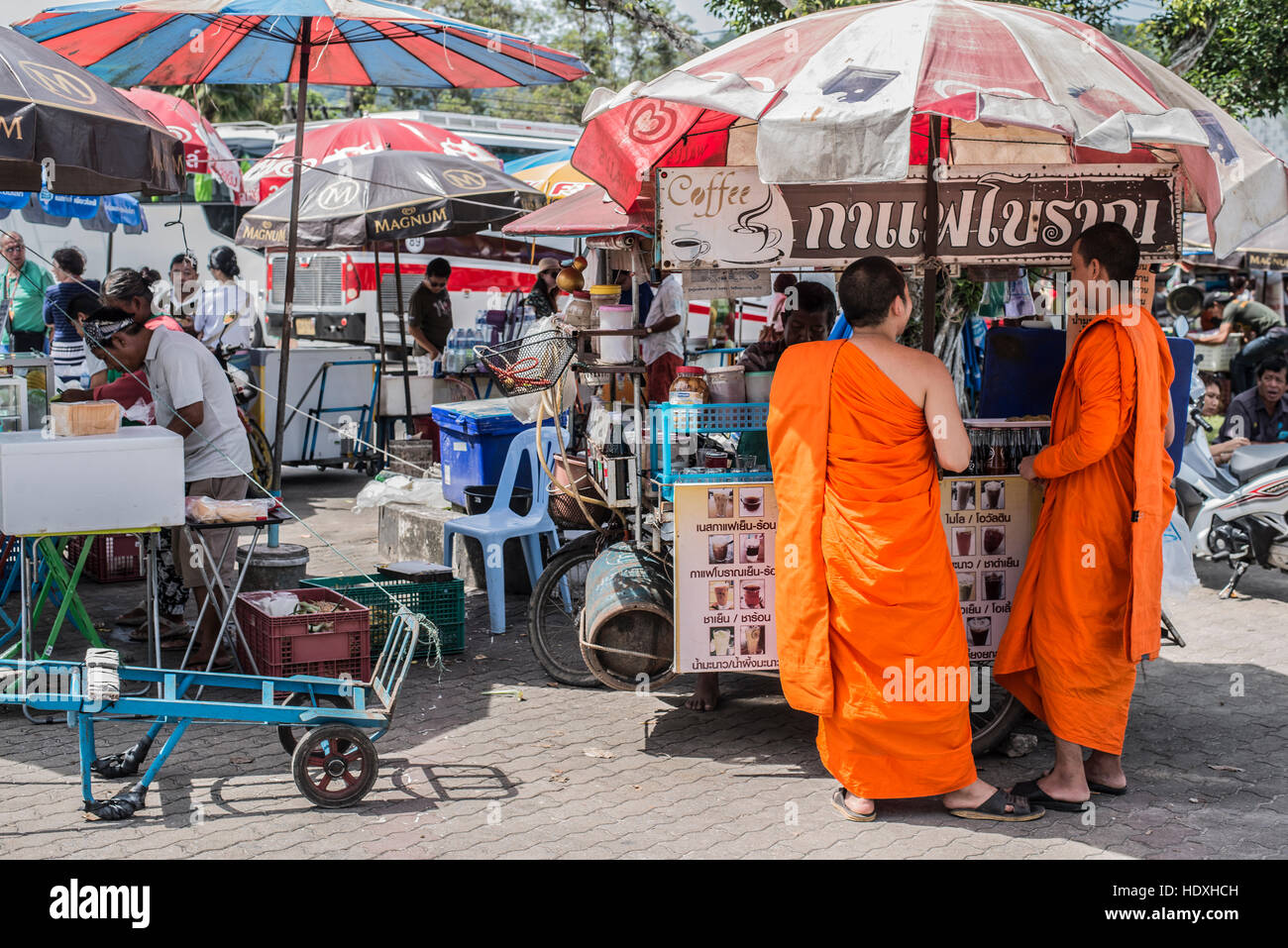 Unidentified monks receive food offering from people on November 24, 2014 in Phuket, Thailand. Offering food is - Stock Image