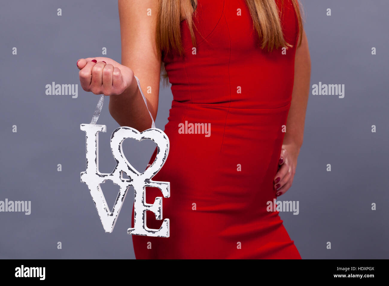 Valentines Day. Woman wearing red dress holding sign love symbol on grey background - Stock Image