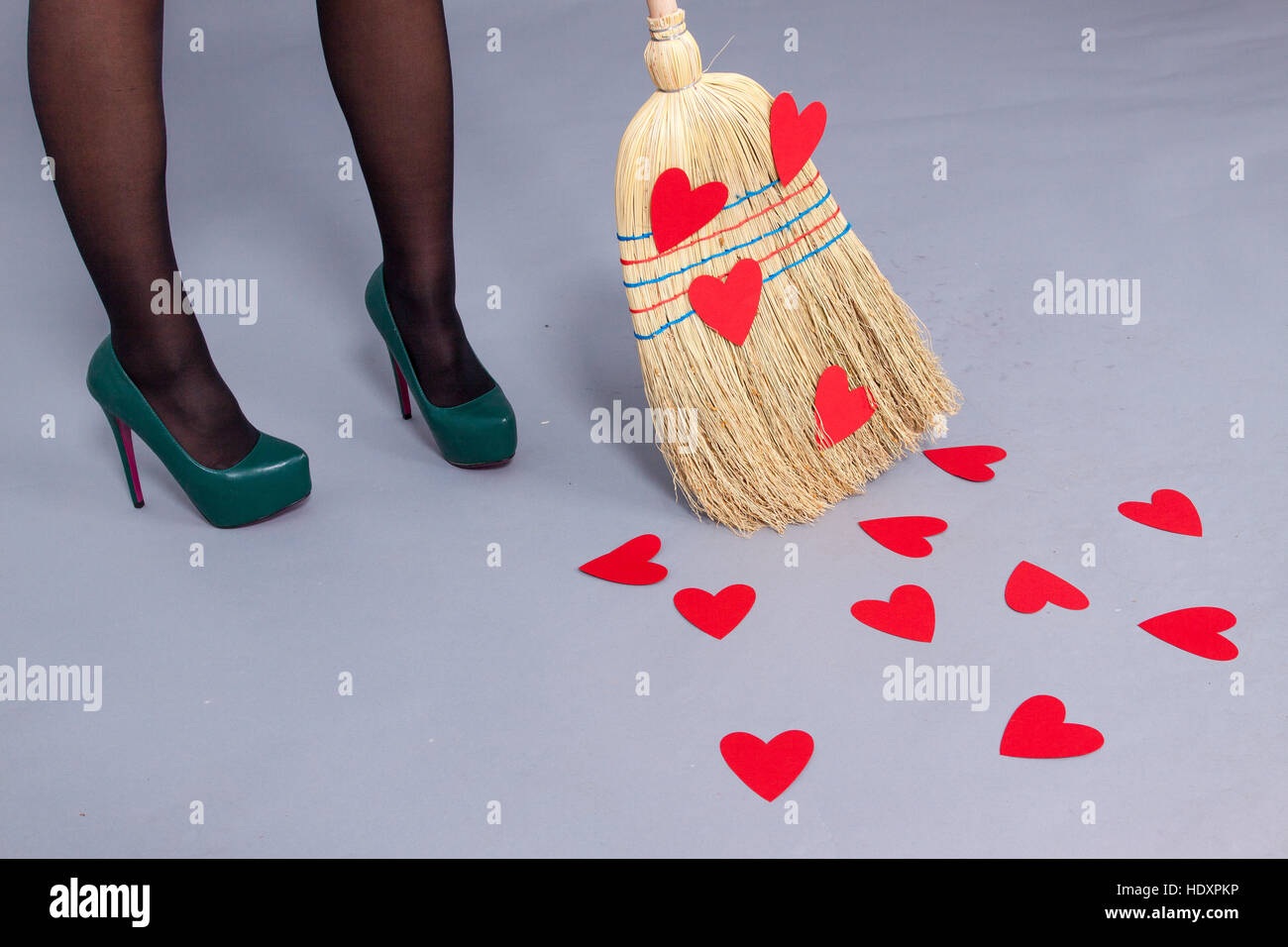 Holiday St.Valentine's Day, beautiful woman posing with red hearts made of paper on the broom - Stock Image