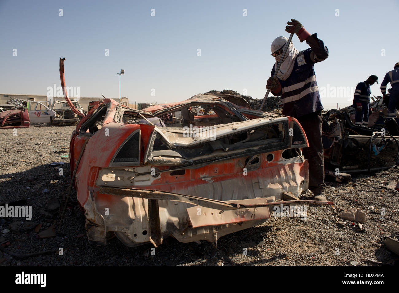 Migrant worker breaking up cars for recycling - Stock Image