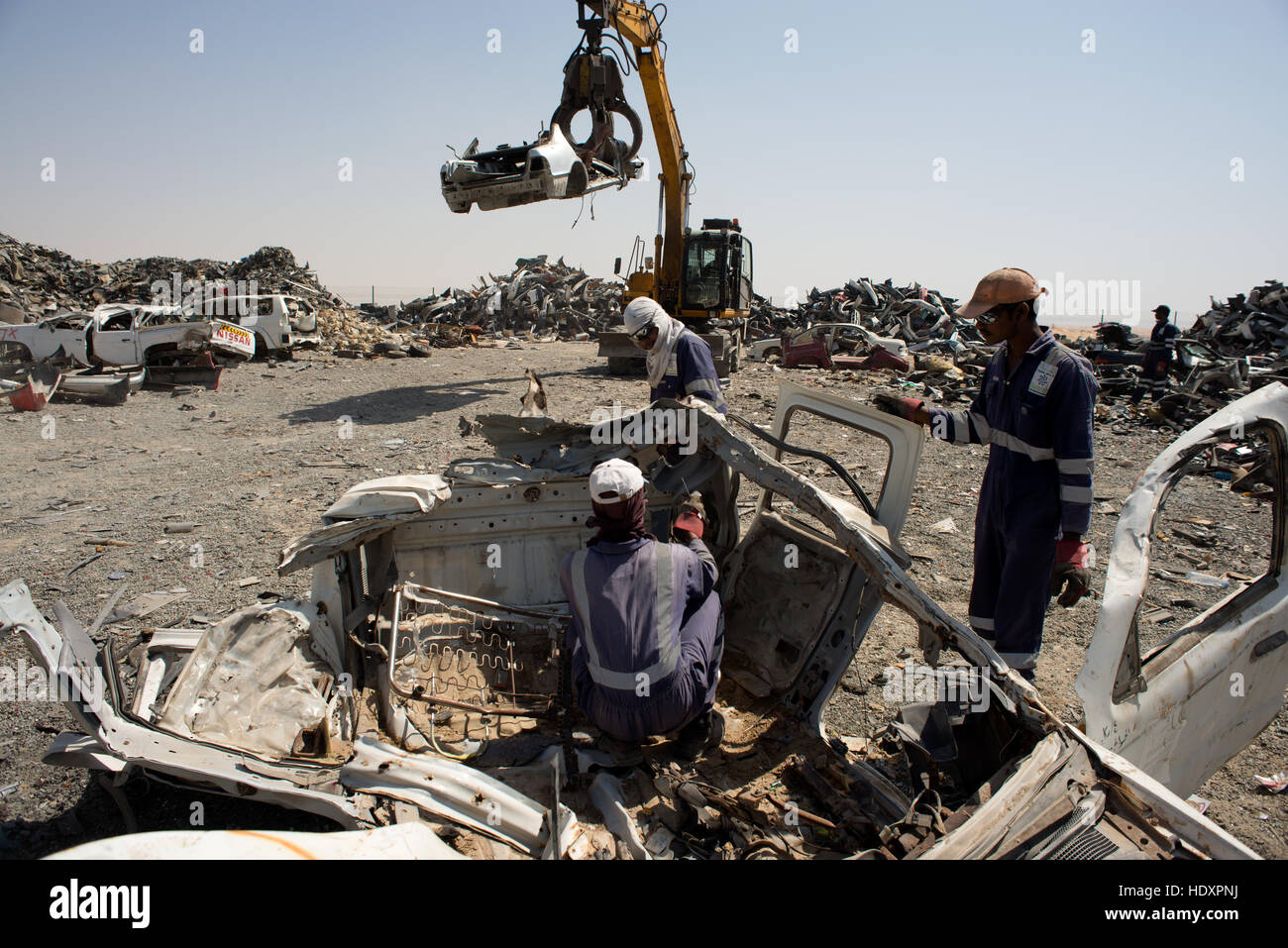 Migrant workers dismantle cars for recycling - Stock Image