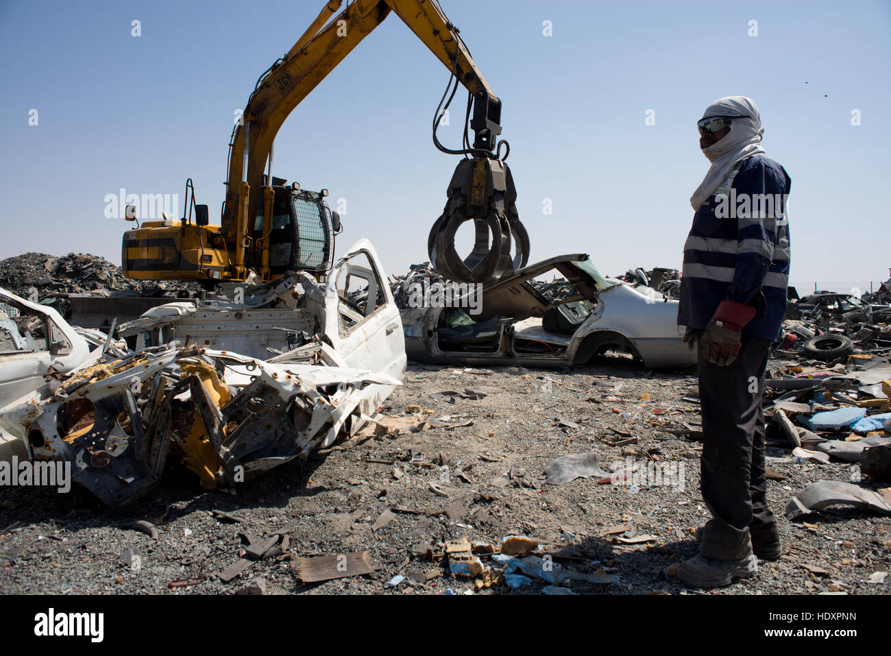 Migrant worker watches as car is crushed for recycling, UAE - Stock Image