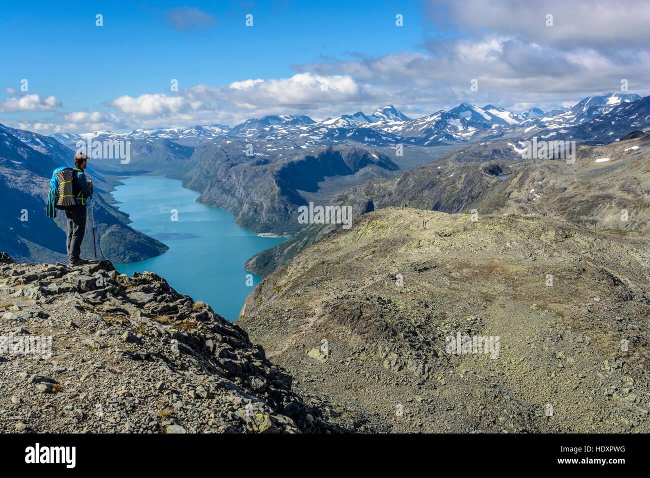 Hiker on the Besseggen ridge overlooking Gjende lake, Jotunheimen National Park, Norway - Stock Image