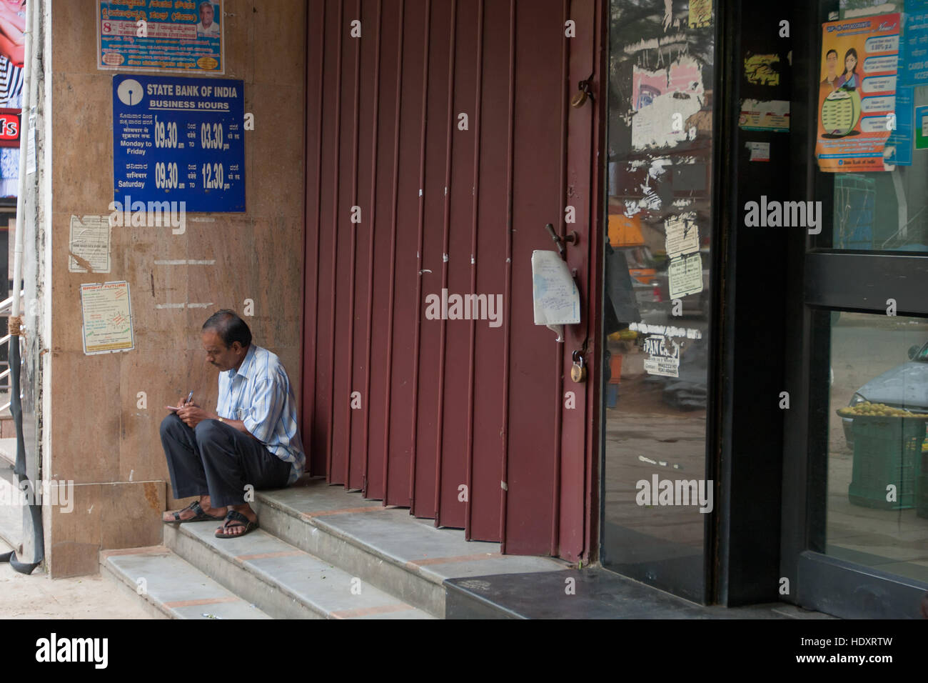 Man waiting in front of a bank to open, Bangalore, India (photo taken before demonetization 2016) - Stock Image