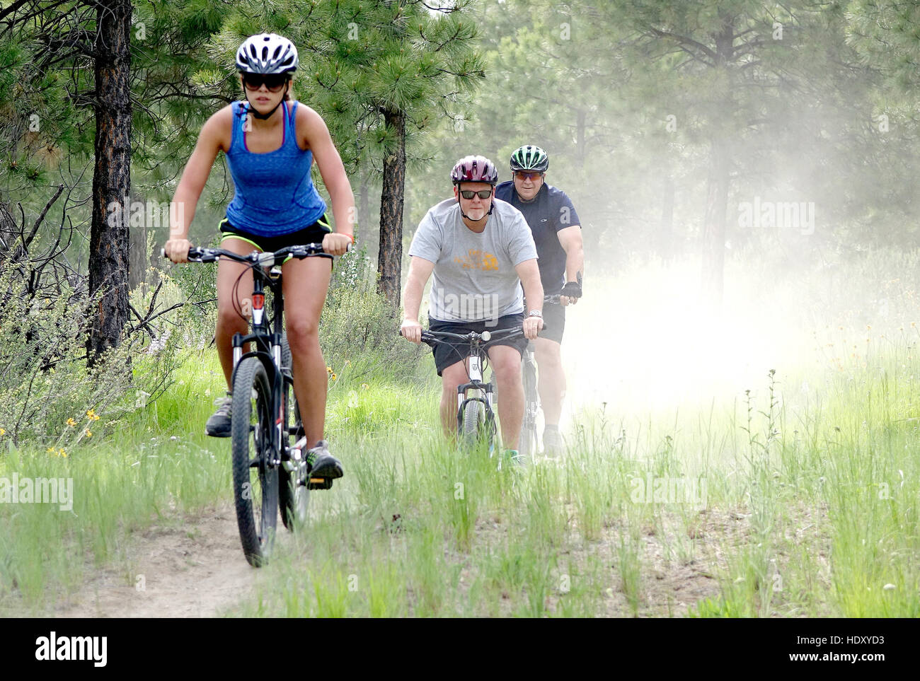 Three mountain bikers on a dusty trail. - Stock Image