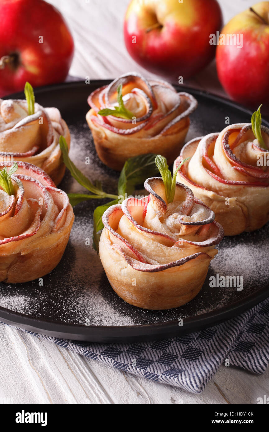 Delicious apple cake in the form of roses. Festive pastry, vertical close-up - Stock Image