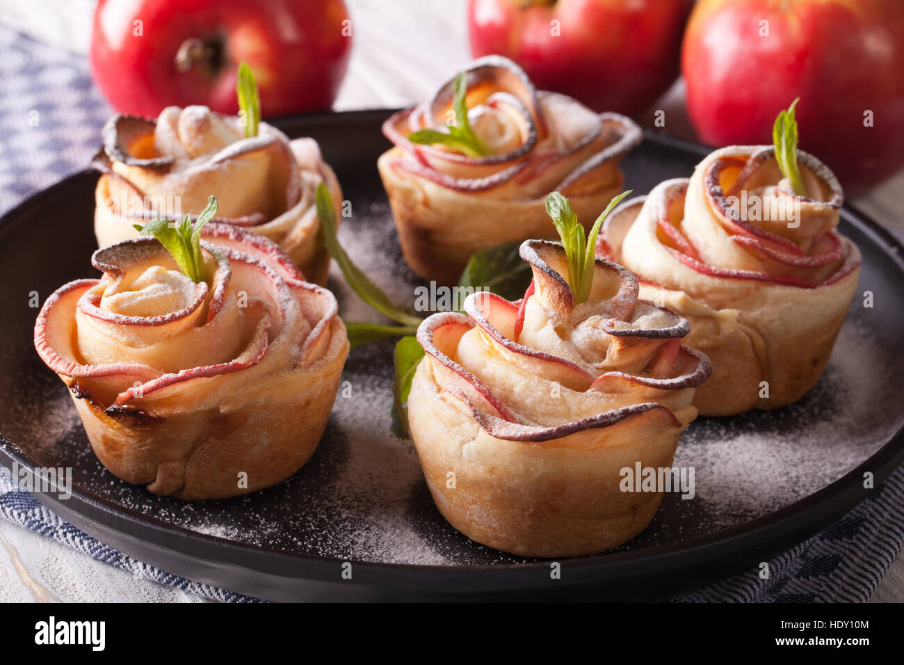 Beautiful apple cake in the form of roses. Festive pastry, horizontal closeup - Stock Image