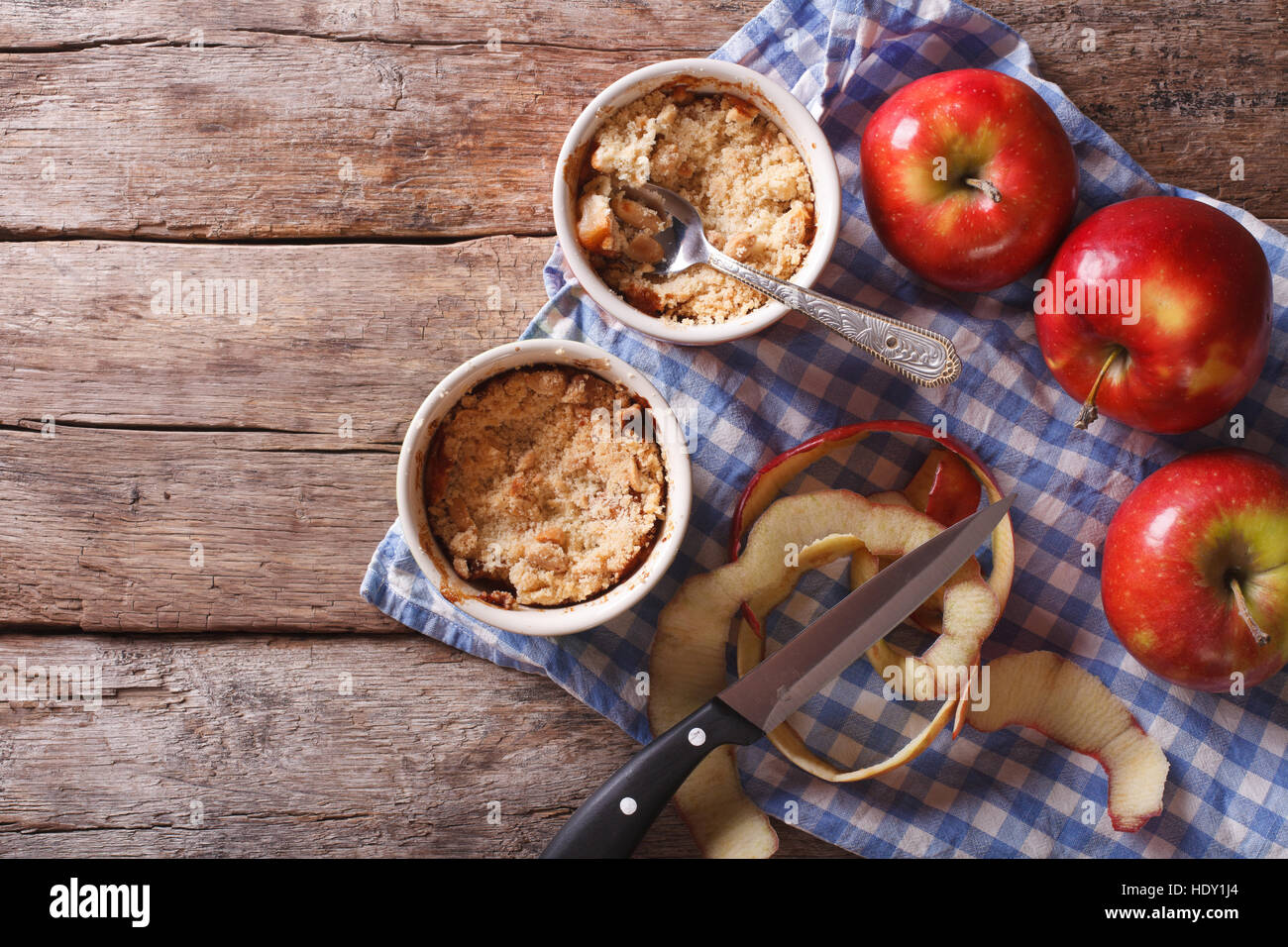 Traditional apple crumble in the pot on the table. horizontal view from above, rustic style Stock Photo