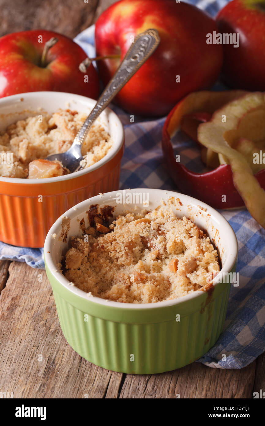 English crumble with apples close-up in the pot. vertical rustic style - Stock Image