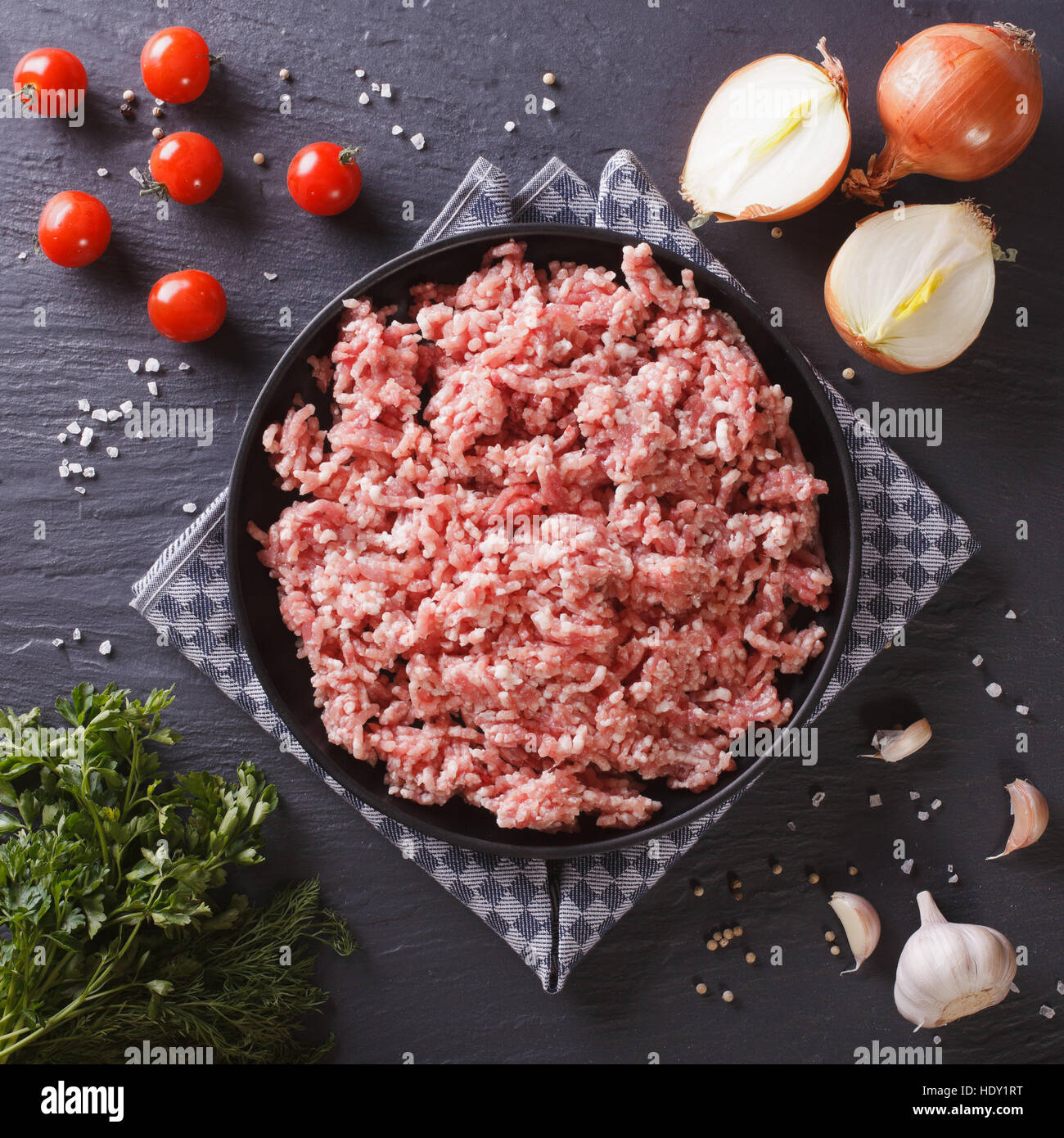 Raw minced pork in a plate and fresh vegetables on a table close-up. top view Stock Photo