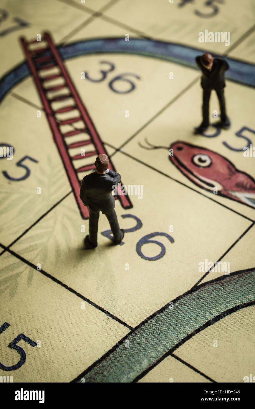 Business men pondering success and failure on a snakes and ladders board a problem solving concept - Stock Image