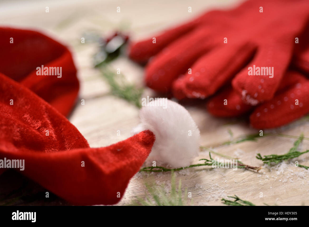 closeup of a santa hat, a pair of cozy red gloves, some twigs of pine tree and a twig of holly in the background, - Stock Image