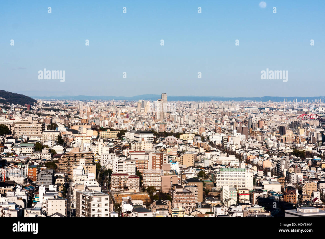 Japan, Kobe. Daytime moon in clear blue sky, seen over Kobe city. High viewpoint, cityscape, endless urban sprawl. - Stock Image
