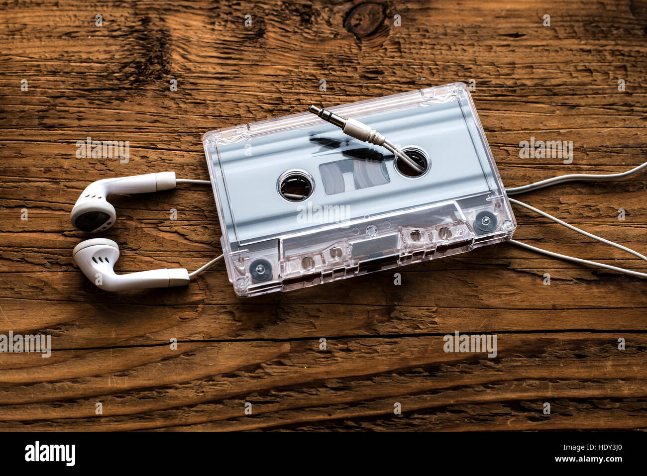 Retro compact cassette with rolls and white micro headphones on wooden table texture. Audio background Stock Photo