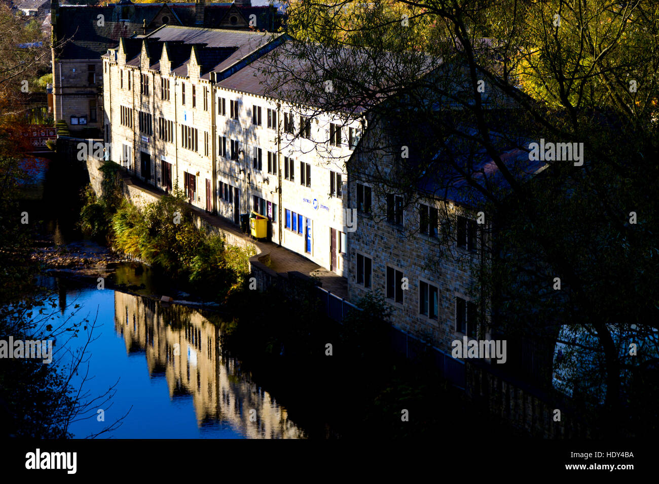 A row of buildings reflected in the calm waters of Hebden Beck, Hebden Bridge, Calderdale, West Yorkshire, UK - Stock Image