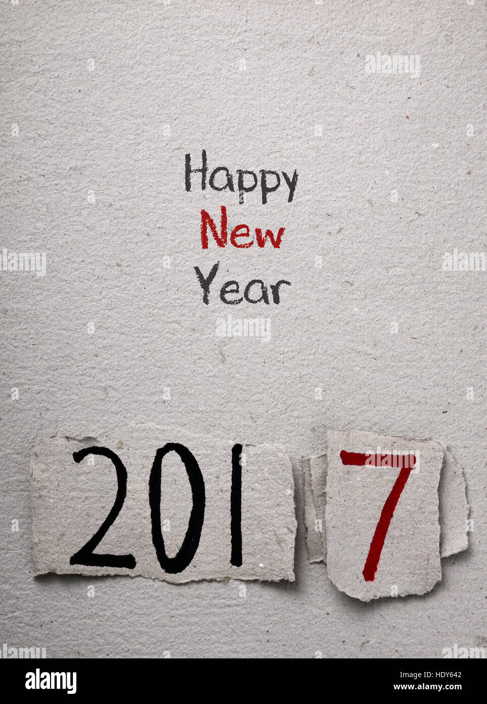 the text happy new year written in a rustic paper and the number 2017, as the new year, handwritten in black and - Stock Image