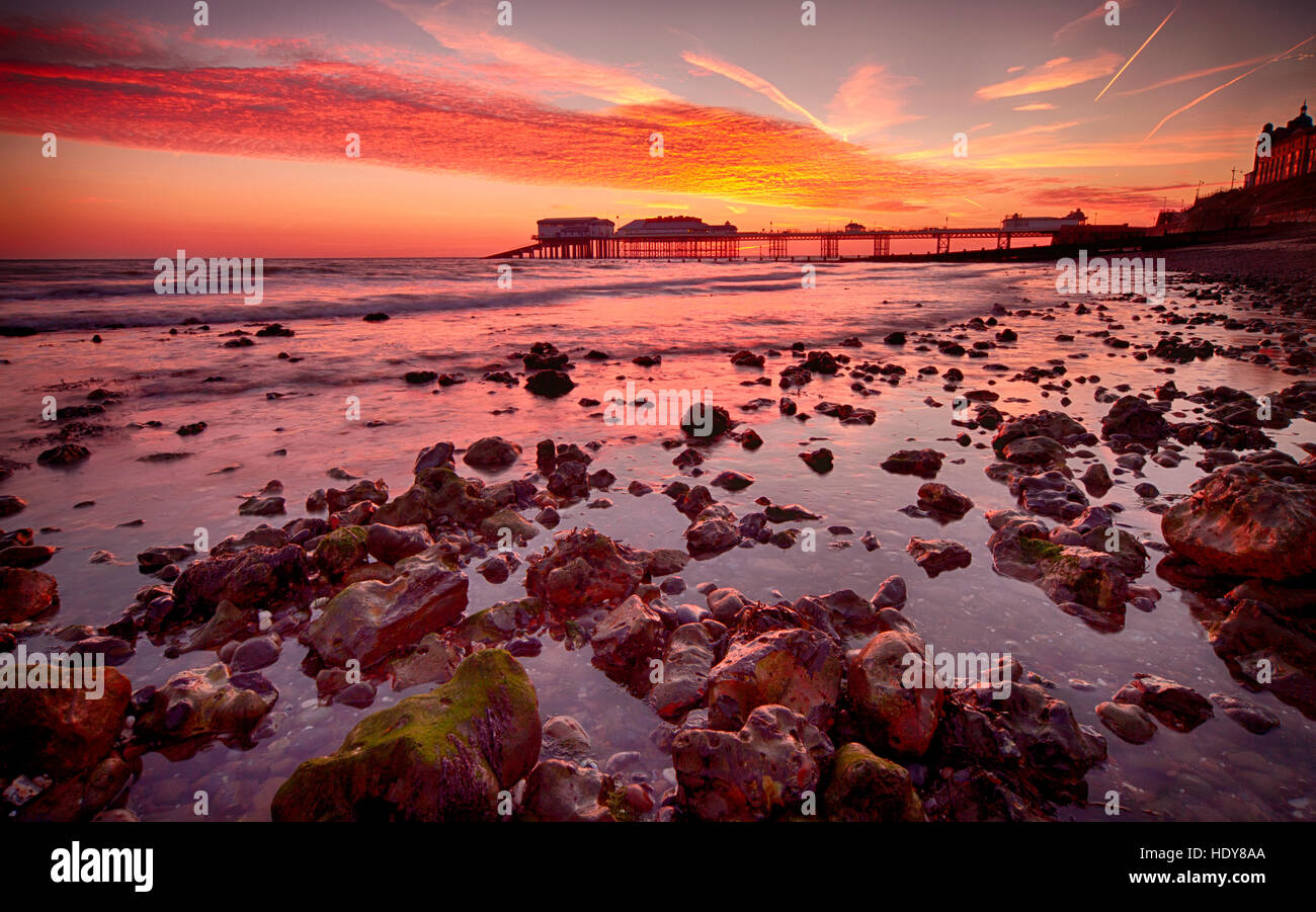 Sunrise over Cromer Pier, home to the Cromer Lifeboat Station and the Pavilion Theatre, on the Norfolk coast - Stock Image
