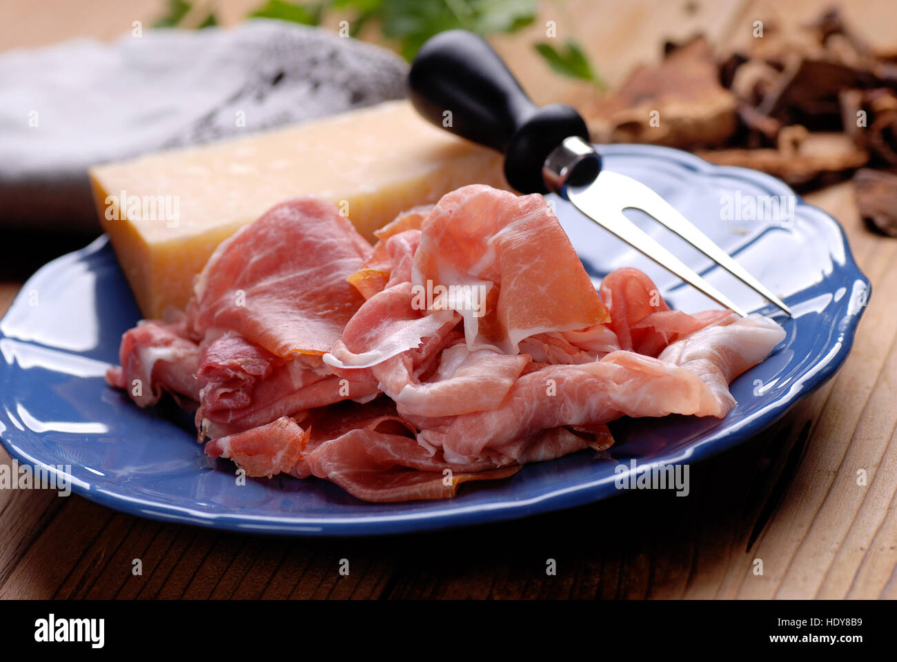 Parma ham and Parmesan cheese on blue plate - Stock Image