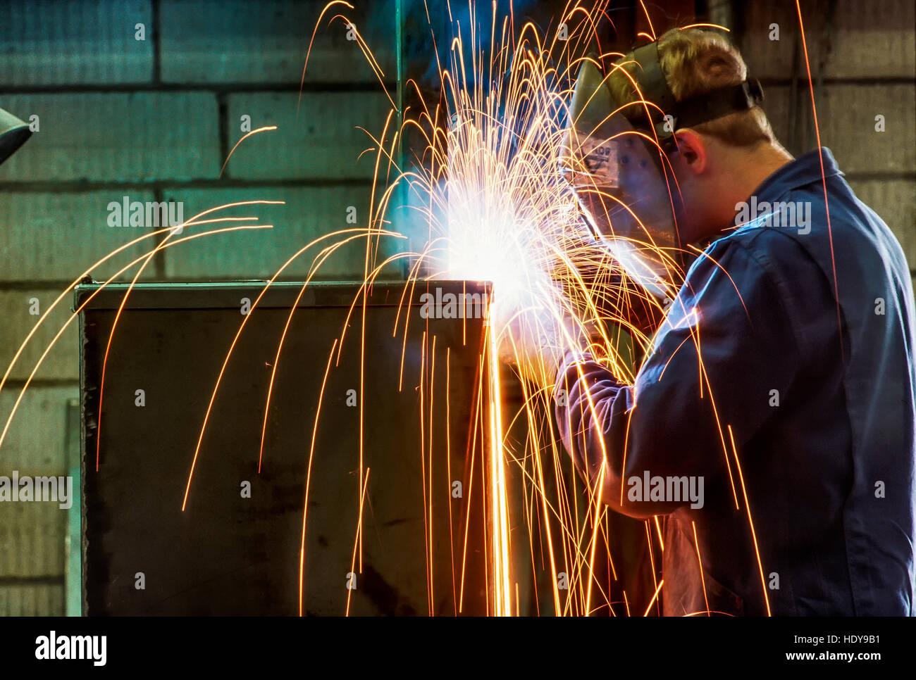 Acetylene welder working on a furnace unit in a German machine factory. - Stock Image