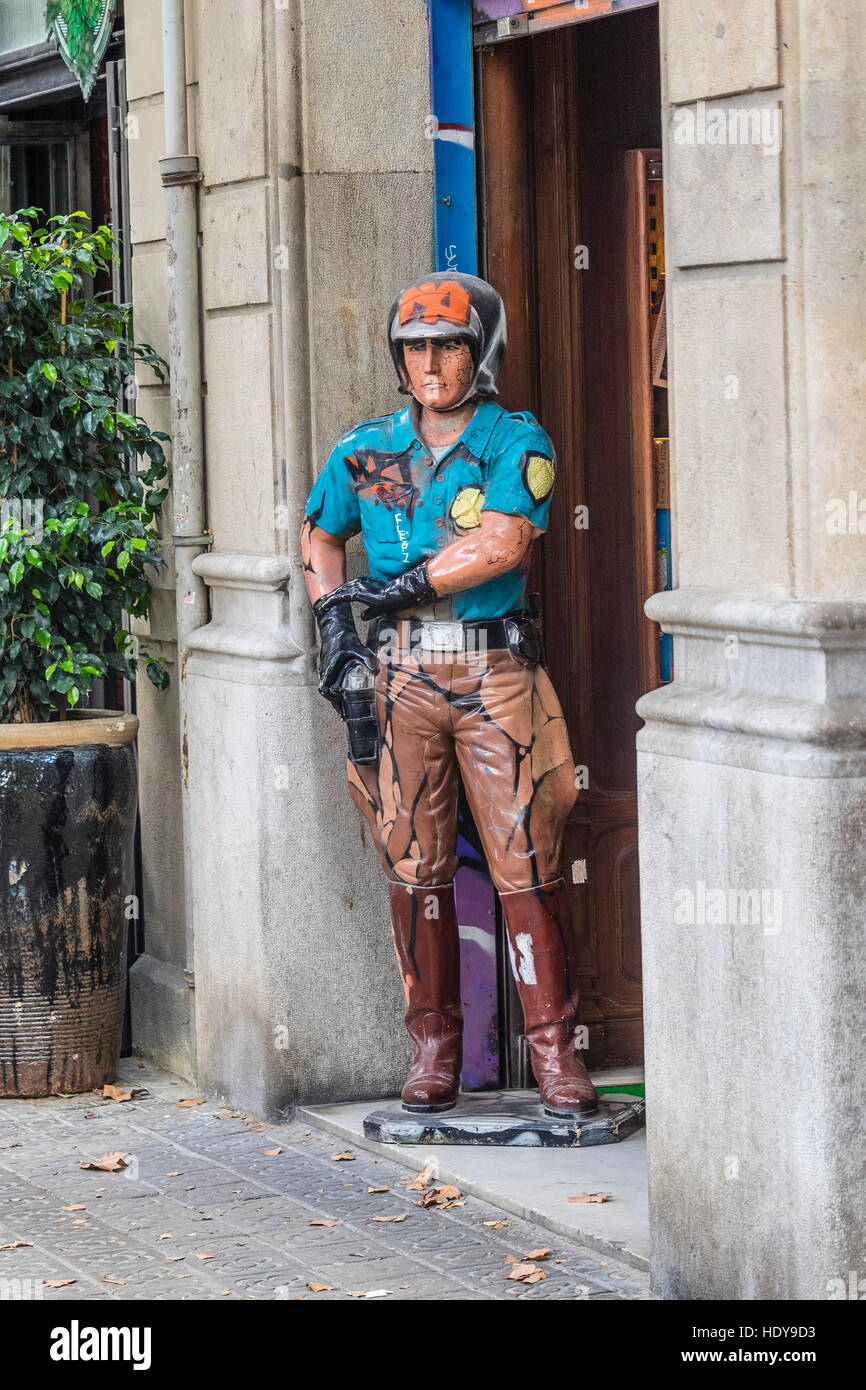A very lifelike statue of a policeman standing in a doorway in Barcelona, Spain. - Stock Image