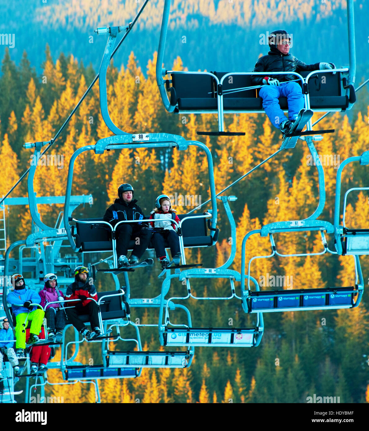 Skiers and snowboarders on a ski lift in Bukovel. Bukovel is the most popular ski resort in Ukraine. Stock Photo