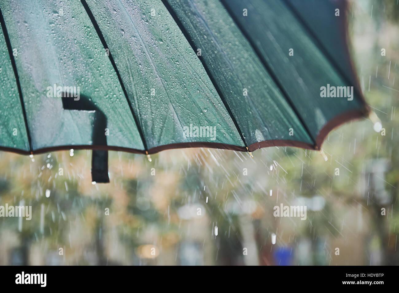 Rain drops falling from the umbrella. Cloudy, damp. - Stock Image