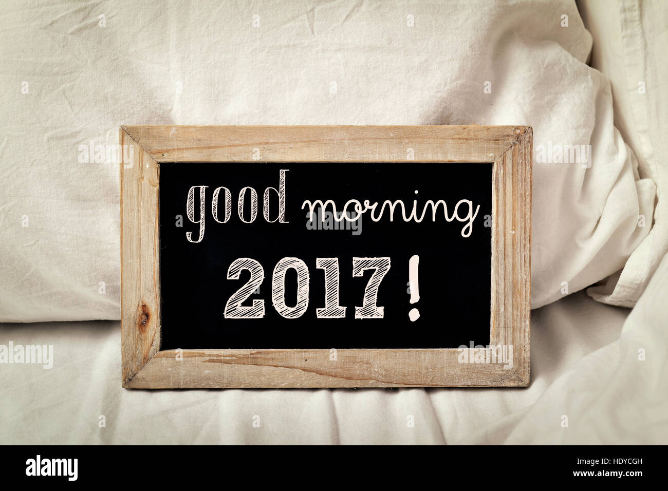 a wooden-framed chalkboard with the text good morning 2017 written in it, placed on a bed set with white bedlinen - Stock Image