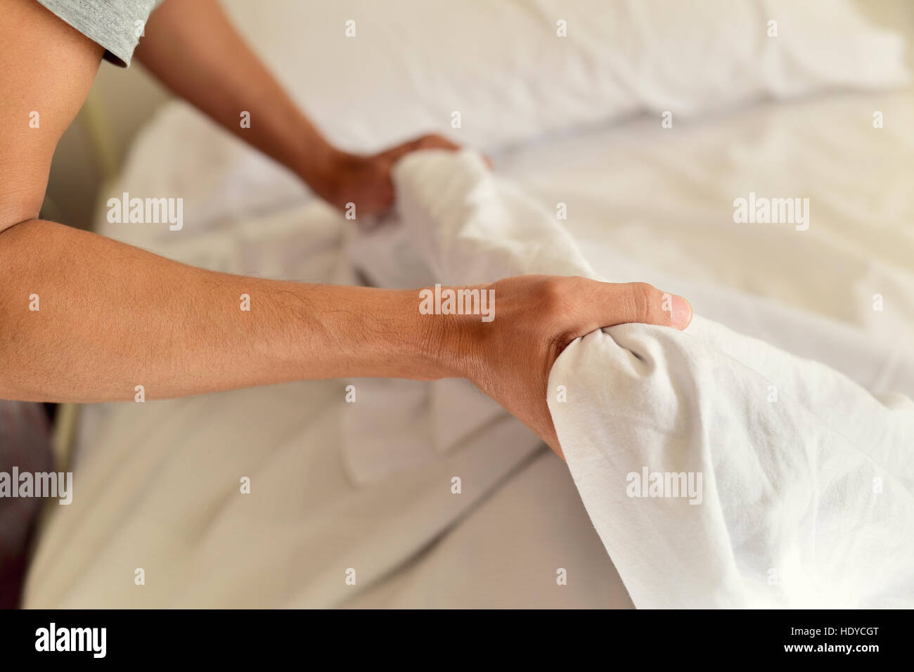 closeup of a young man extending the bedsheet or the duvet on the mattress as he is making the bed - Stock Image