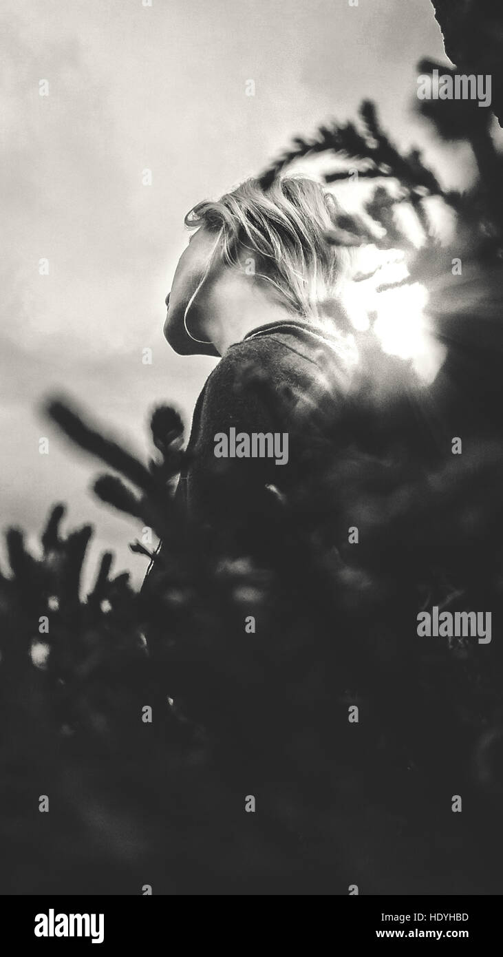 black and white image of woman siting by the rock - Stock Image