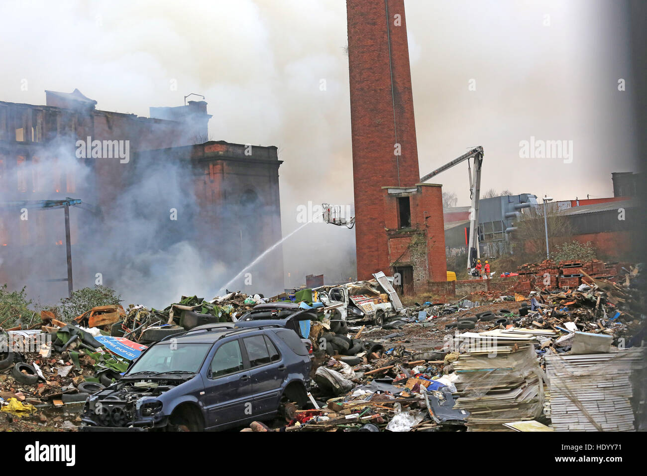 Oldham, UK. 15th Dec, 2016. A yard full of debris and old cars at the scene of a mill fire on Cardwell Street, Oldham, Stock Photo