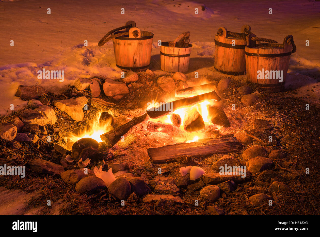 Evening Bonfire and Four Wooden Water Buckets in the Snow - Stock Image