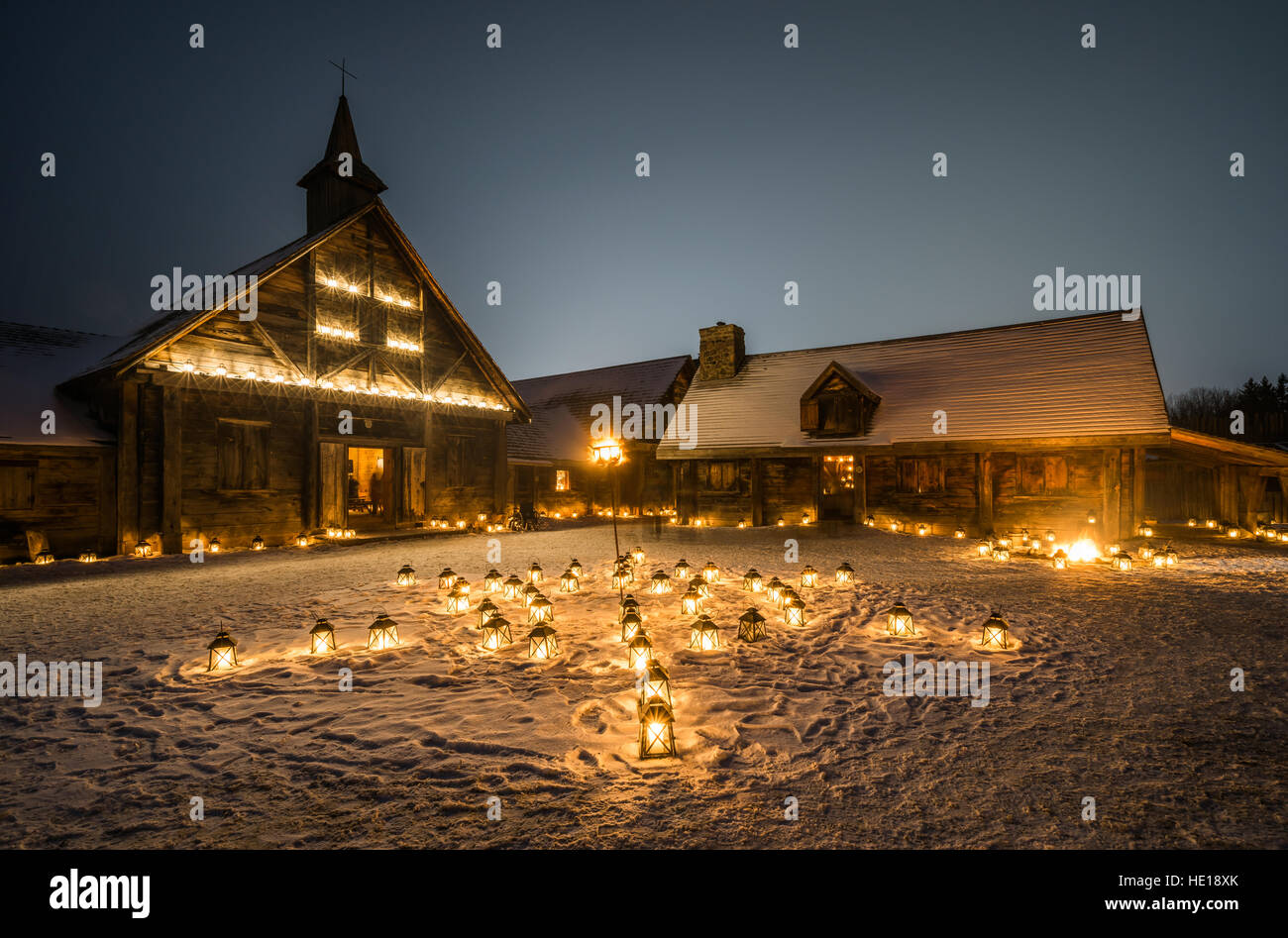 Rustic Cabins at Twilight Illuminated by the Glow of Candle Lanterns at Christmas time - Stock Image