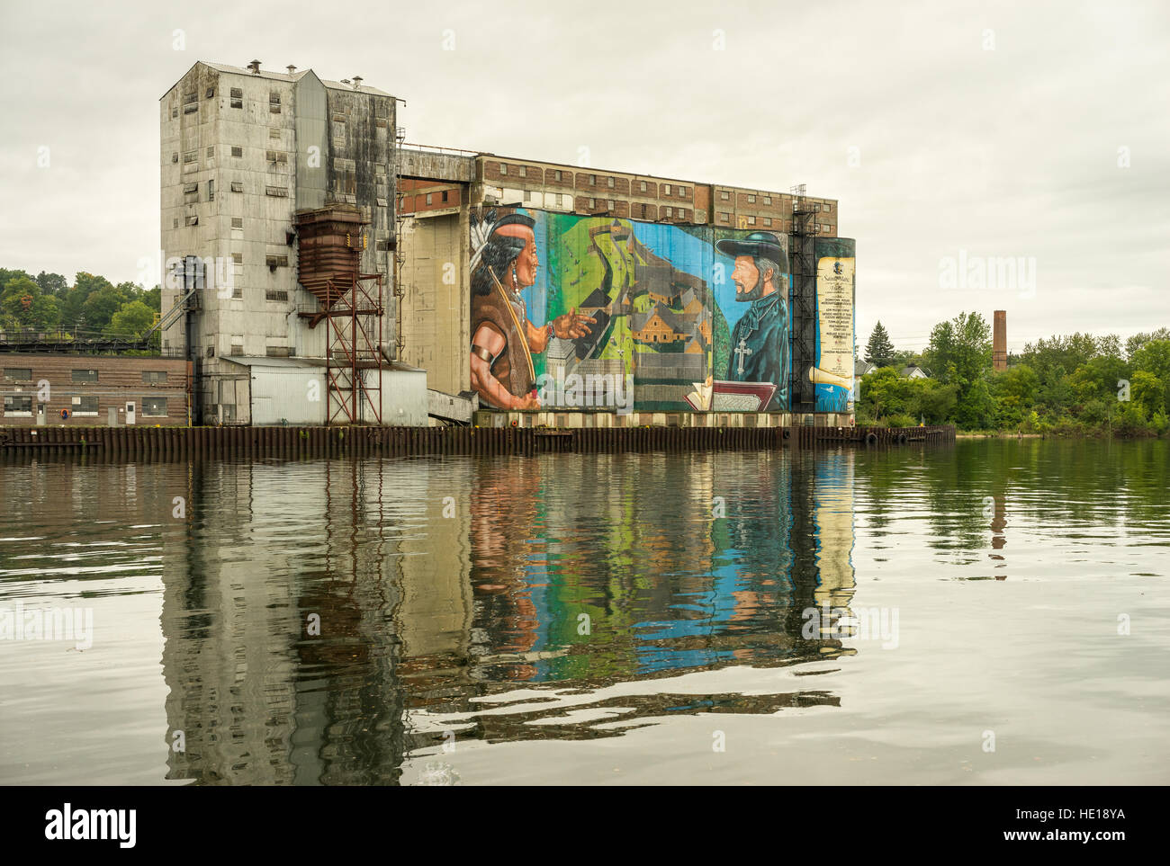 Grain Elevators With Colourful Painting Reflected in Harbour Water - Stock Image