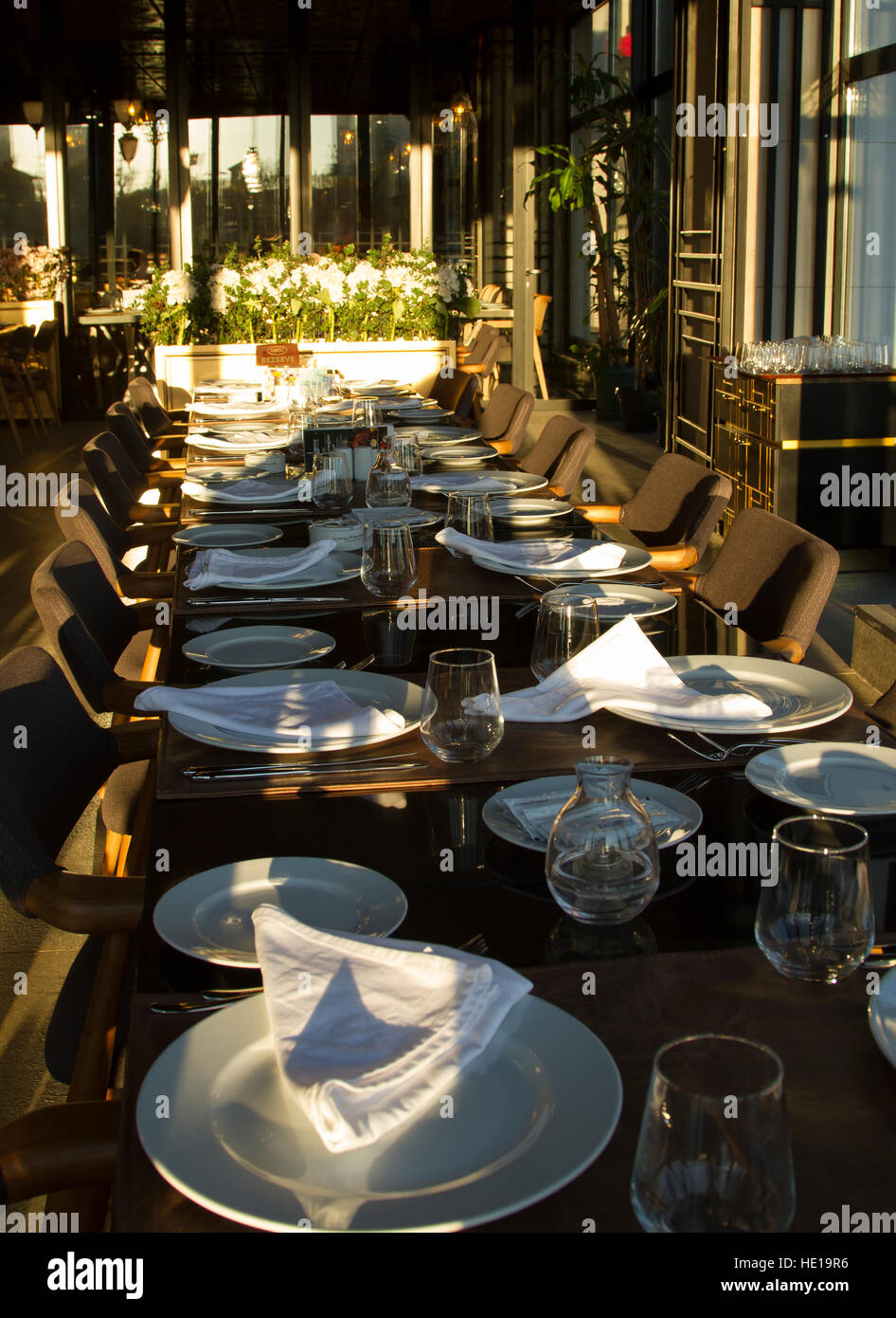 Long table in the restaurand served for several persons with glasses, plates - Stock Image