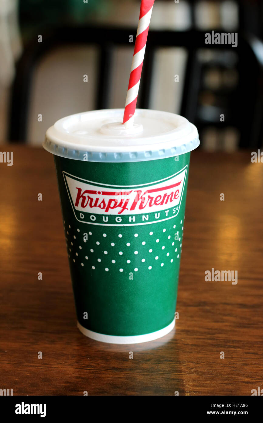 Krispy Kreme cold drink in a  paper cup on wooden table - Stock Image