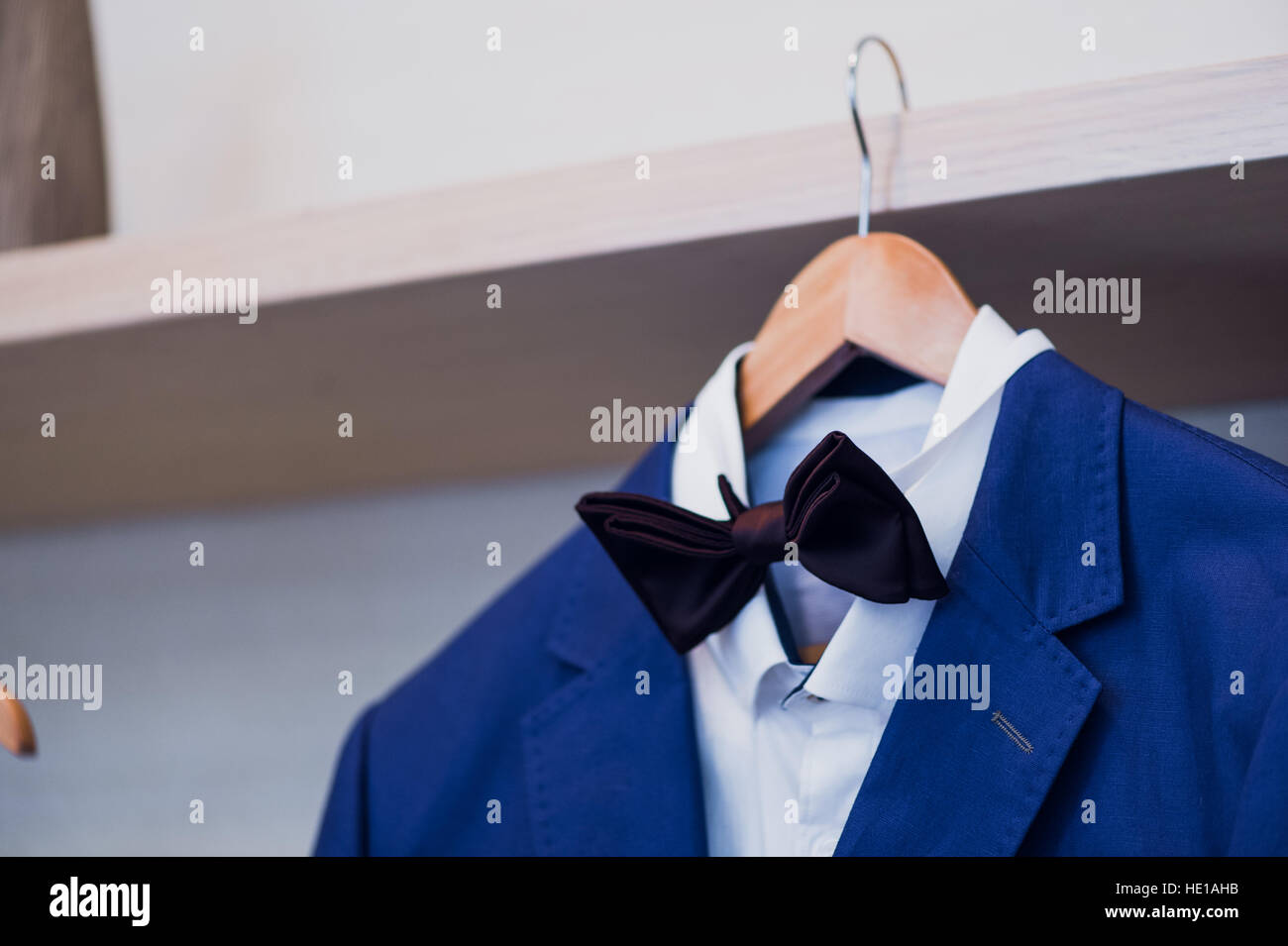 Close-up of blue jacket with bow tie on a hanger. Stock Photo
